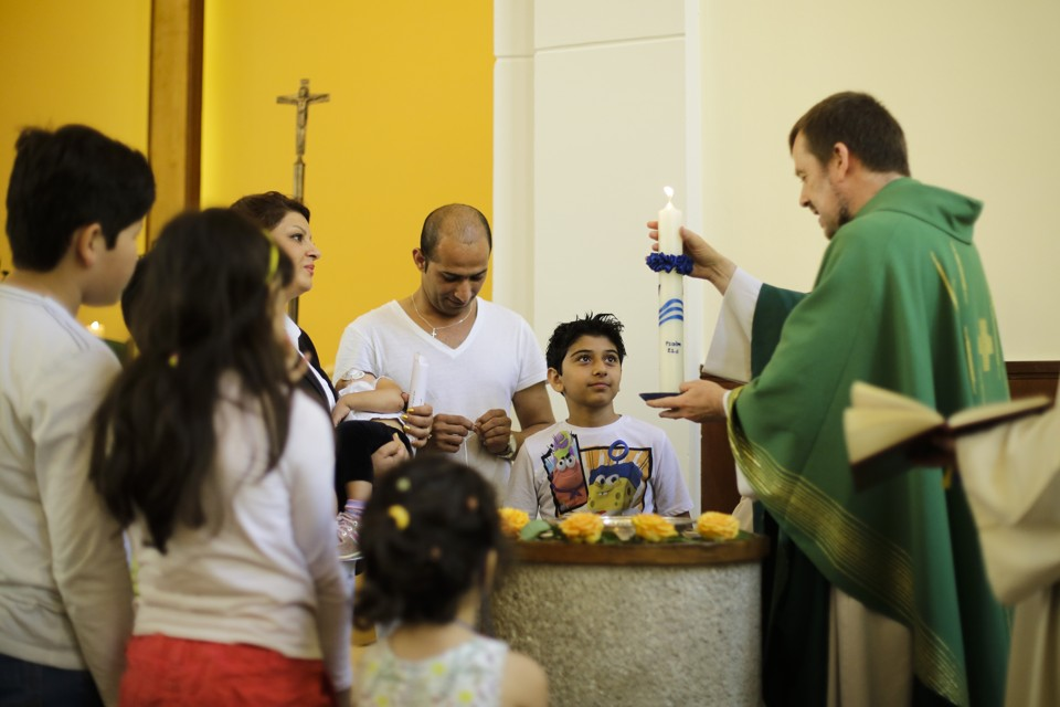 Pastor Gottfried Martens lights a candle during a service to baptize people from Iran, in the Trinity Church in Berlin, Aug. 30, 2015. Third right is Iranian asylum-seeker Mohammed Ali Zanoobi. He is one of hundreds of mostly Iranian and Afghan asylum seekers who have converted to Christianity at the evangelical Trinity Church in the leafy Berlin neighborhood. Most say true belief prompted their embrace of Christianity, but there's no overlooking the fact that the decision will also greatly boost their chances of winning asylum by allowing them to claim they would face persecution if sent home. (AP Photo/Markus Schreiber)